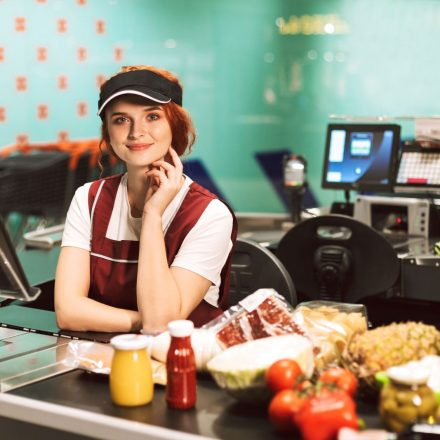 young-smiling-female-cashier-in-uniform-dreamily-Z74XGMA